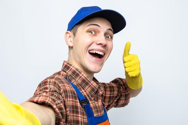 Glimlachend met duim omhoog jonge schoonmaakster die uniform en pet met handschoenen draagt