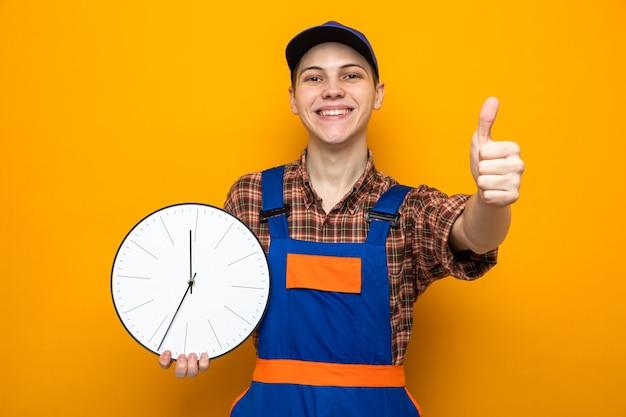Glimlachend met duim omhoog jonge schoonmaakster met uniform en pet met wandklok