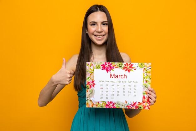 Glimlachend met duim omhoog mooi jong meisje op gelukkige vrouwendag met kalender geïsoleerd op oranje muur