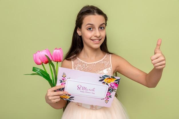 Glimlachend met duim omhoog mooi klein meisje op gelukkige vrouwendag met bloemen met wenskaart