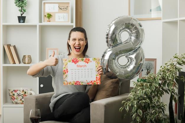 Glimlachend met duim omhoog mooie vrouw op gelukkige vrouwendag met kalender zittend op een fauteuil in de woonkamer