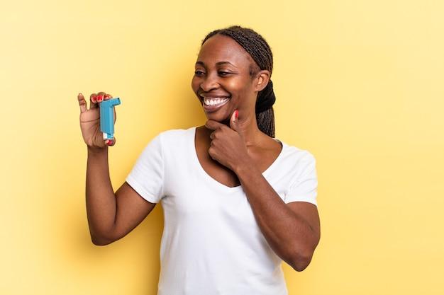 Glimlachend met een gelukkige, zelfverzekerde uitdrukking met de hand op de kin, zich afvragend en opzij kijkend. astma concept