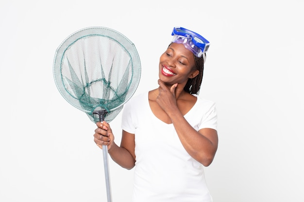 Glimlachend met een vrolijke, zelfverzekerde uitdrukking met de hand op de kin met een veiligheidsbril en een vissersnet