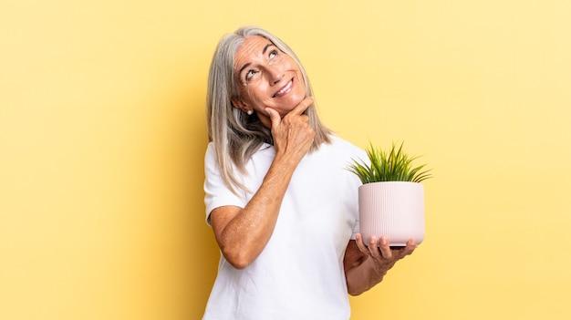 Glimlachend met een vrolijke, zelfverzekerde uitdrukking met de hand op de kin, zich afvragend en opzij kijkend met een decoratieve plant