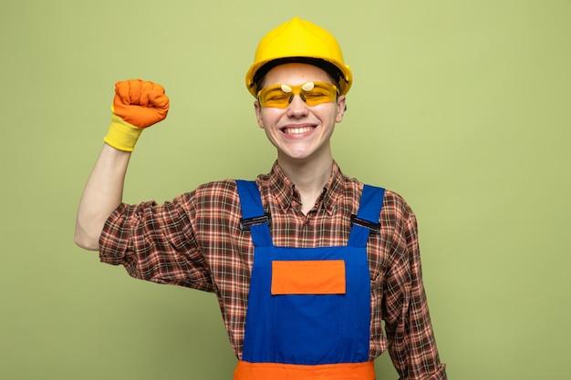 Glimlachend met gesloten ogen die de hand opheft, jonge mannelijke bouwer met uniform en handschoenen met bril
