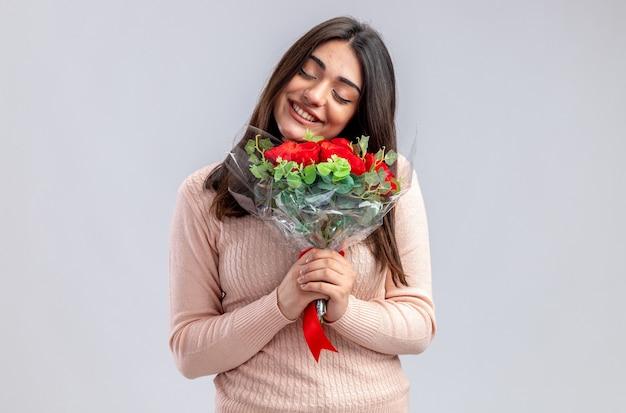 Glimlachend met gesloten ogen hoofd kantelen jong meisje op valentijnsdag met boeket geïsoleerd op een witte achtergrond