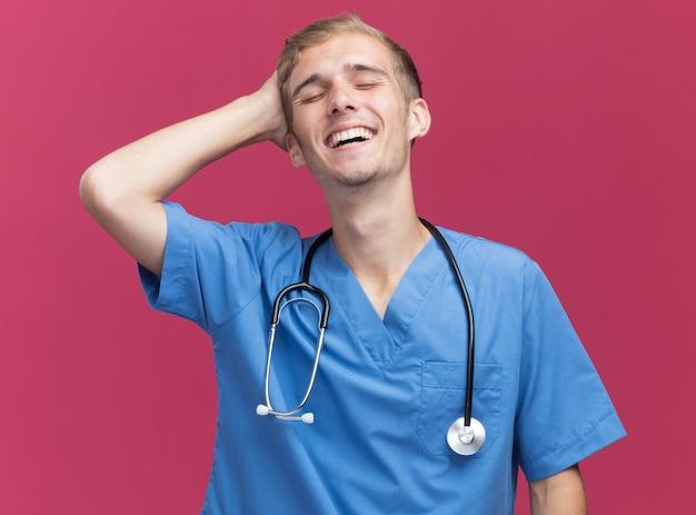 Glimlachend met gesloten ogen jonge mannelijke arts die doktersuniform draagt met een stethoscoop die hand op het hoofd zet geïsoleerd op roze muur