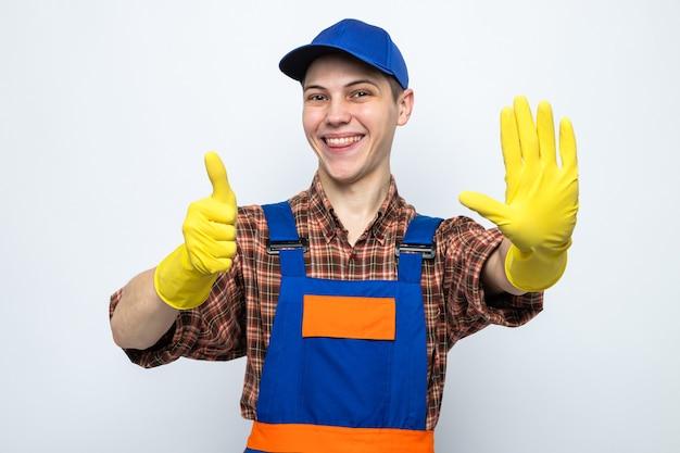 Glimlachend met stopgebaar zijn duim omhoog jonge schoonmaakster die uniform en pet met handschoenen draagt