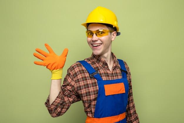 Glimlachend met vijf jonge mannelijke bouwer die uniform en handschoenen met een bril draagt
