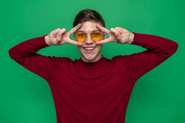 Glimlachend met vredesgebaar jonge knappe kerel met een bril geïsoleerd op een groene muur