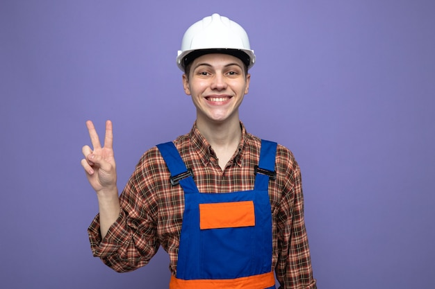 Glimlachend met vredesgebaar jonge mannelijke bouwer die uniform draagt