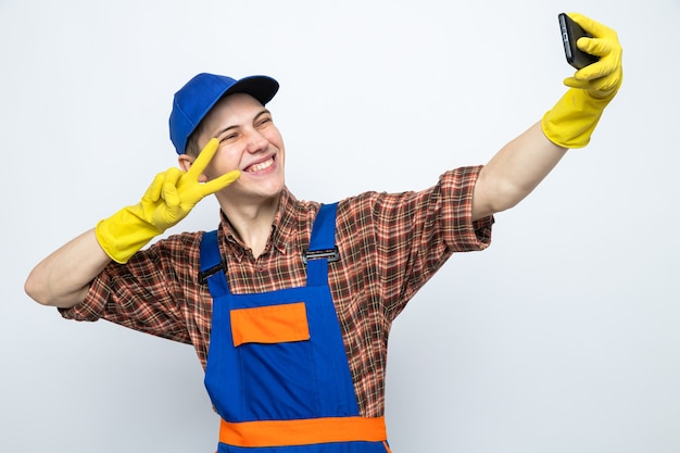 Glimlachend met vredesgebaar, jonge schoonmaakster die uniform draagt en pet met handschoenen neemt een selfie