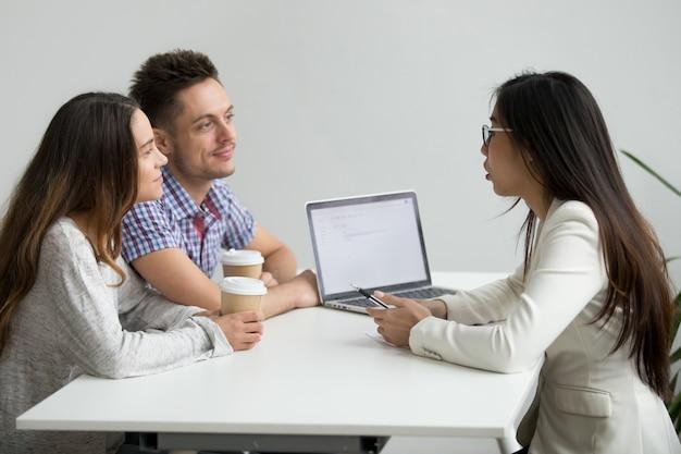 Glimlachend millennial paar die aan aziatische adviseursadvocaat raadplegen die klanten raadplegen