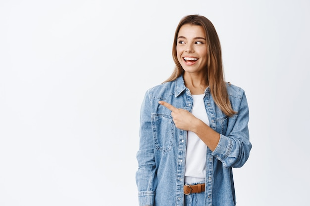 Glimlachend modern meisje in vrijetijdskleding, wijzend en starend naar het logo met een blij gezicht, kijkend naar een goede deal op banner zijwaarts, witte muur