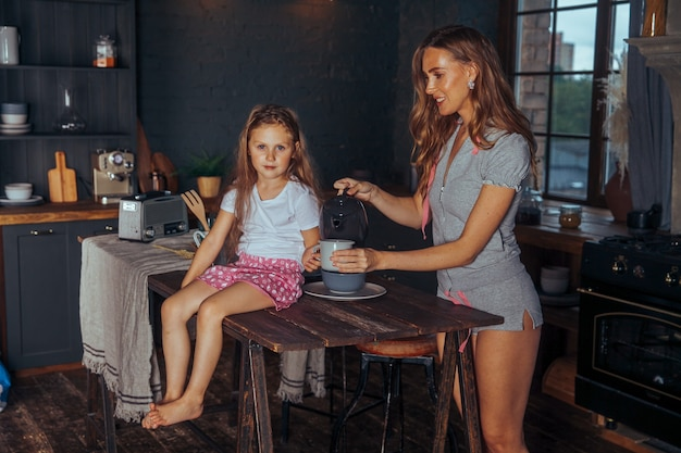 Glimlachend moeder en kind dochter meisje koken en plezier in de donkere keuken