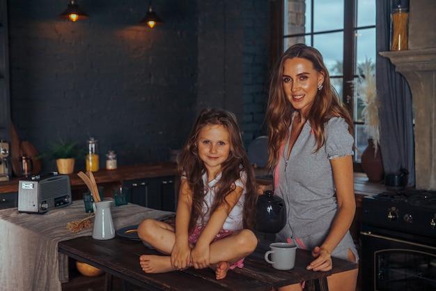 Glimlachend moeder en kind dochter meisje koken en plezier maken in de donkere keuken thuis.
