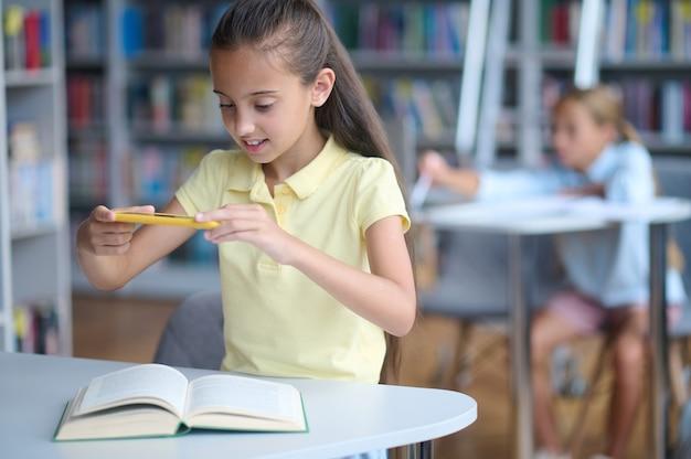 Glimlachend mooi donkerharig schoolmeisje dat foto's maakt van de pagina's in een leerboek met haar smartphone
