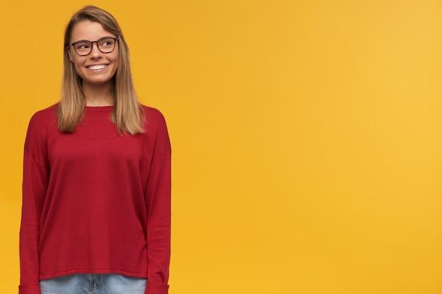 Glimlachend mooi jong charmant blond jong meisje, opzij kijkend op lege exemplaarruimte voor uw advertentie, rode sweater en bril dragen