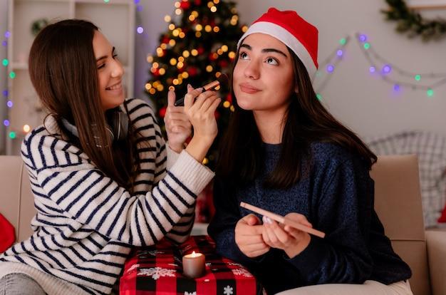 Glimlachend mooi jong meisje doet make-up van haar tevreden vriend met kerstmuts zittend op een fauteuil en genietend van kersttijd thuis