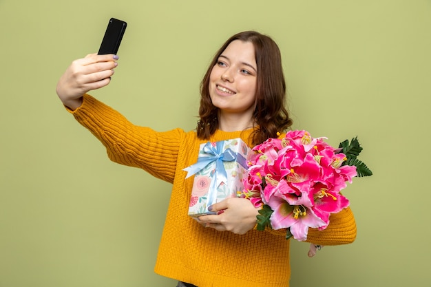 Glimlachend mooi jong meisje met boeket met cadeau neem een selfie