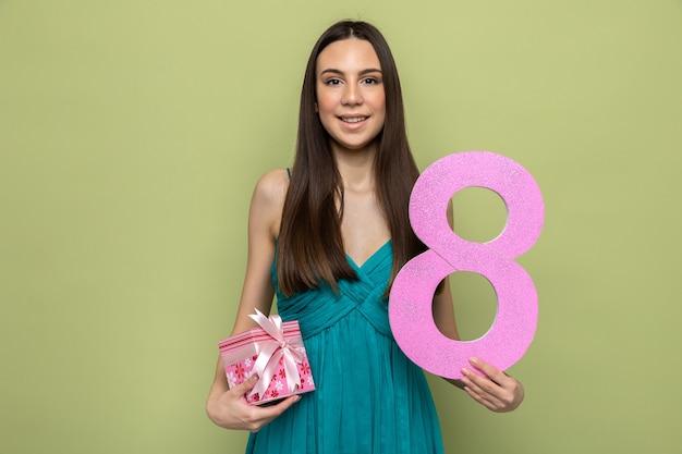 Glimlachend mooi jong meisje op de dag van de gelukkige vrouw met nummer rechtop met cadeau geïsoleerd op olijfgroene muur