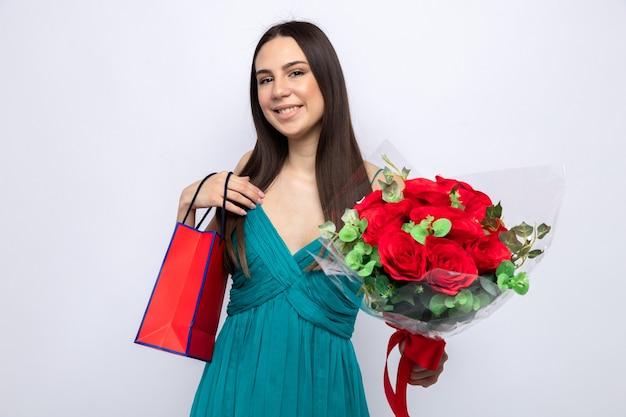 Glimlachend mooi jong meisje op gelukkige vrouwendag met boeket met cadeauzakje geïsoleerd op een witte muur