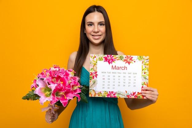 Glimlachend mooi jong meisje op gelukkige vrouwendag met kalender met boeket geïsoleerd op oranje muur