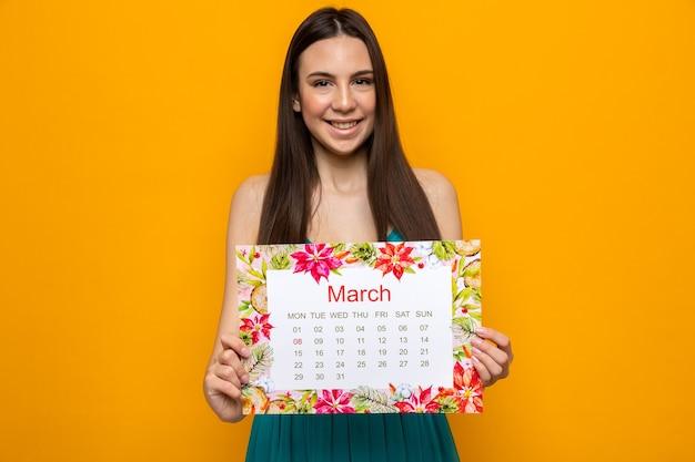 Glimlachend mooi jong meisje op gelukkige vrouwendag met kalender