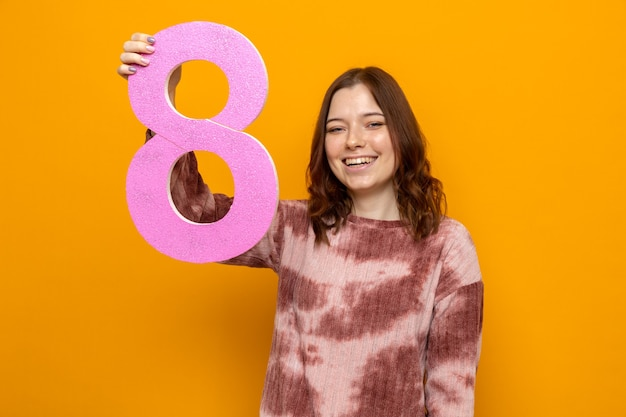 Glimlachend mooi jong meisje op gelukkige vrouwendag met nummer acht geïsoleerd op oranje muur