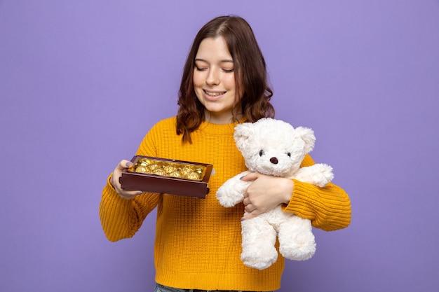Glimlachend mooi jong meisje op gelukkige vrouwendag met teddybeer kijkend naar doos snoep in haar hand geïsoleerd op blauwe muur