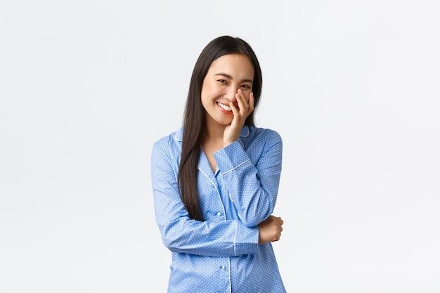 Glimlachend mooi koreaans meisje in blauwe pyjama's aanraken van schone, zuivere huid na het aanbrengen van huidverzorgingsproduct, reinigingsmiddel, koket lachen en blozen, zich gelukkig voelen, witte muur