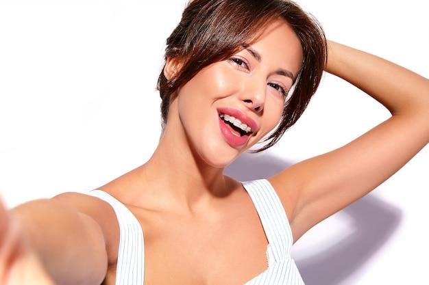 Glimlachend mooi leuk donkerbruin vrouwenmodel in toevallige de zomerkleding zonder make-up met witte steunen op tanden die selfie foto op geïsoleerde telefoon maken