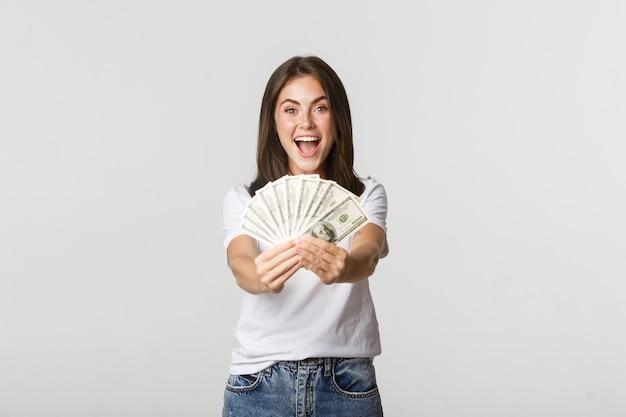 Glimlachend mooi meisje dat u geld geeft