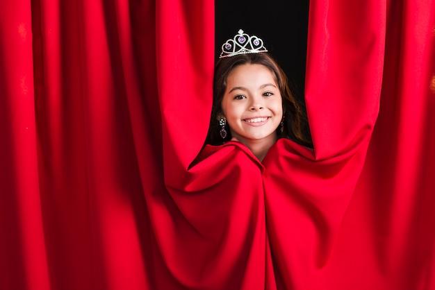 Glimlachend mooi meisje die kroon dragen die van rood gordijn gluren