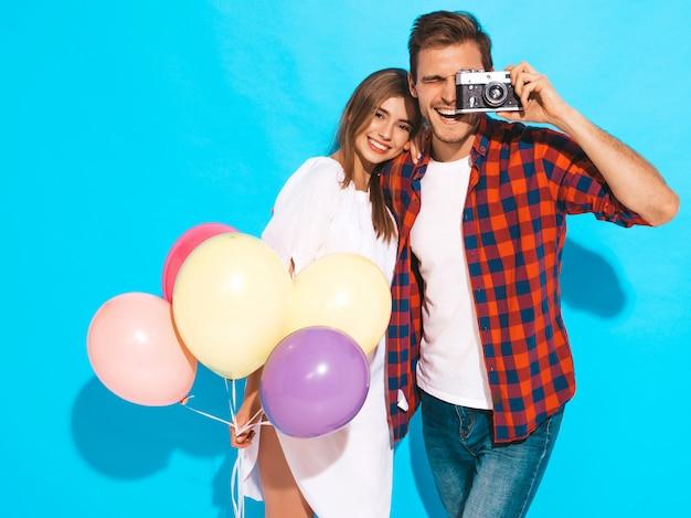 Glimlachend mooi meisje en haar knappe vriendje bedrijf bos van kleurrijke ballonnen. gelukkig paar die foto van zich op retro camera nemen. fijne verjaardag