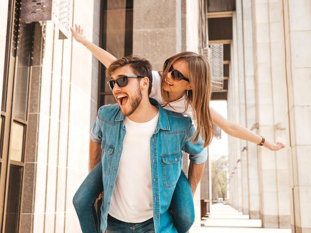 Glimlachend mooi meisje en haar knappe vriendje in casual zomer kleding. man die zijn vriendin op de rug draagt en zij die haar handen opheft.
