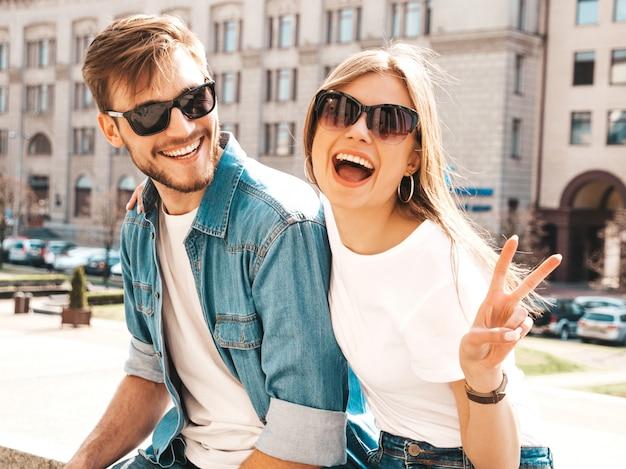 Glimlachend mooi meisje en haar knappe vriendje in casual zomer kleding. . vredesteken tonen