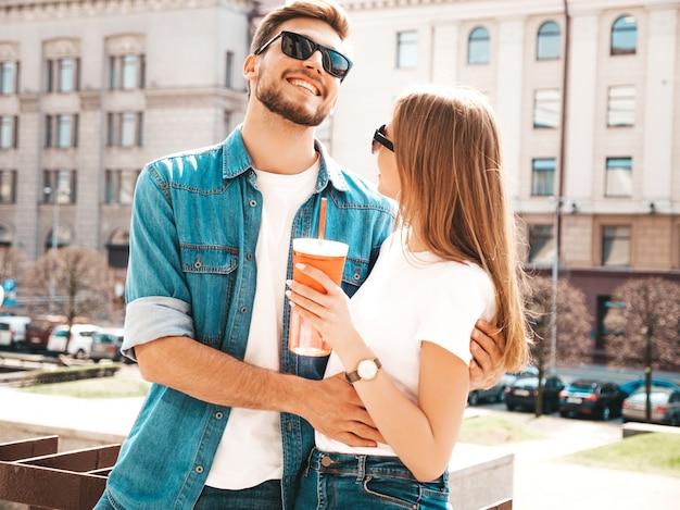 Glimlachend mooi meisje en haar knappe vriendje in casual zomer kleding. . vrouw met fles water