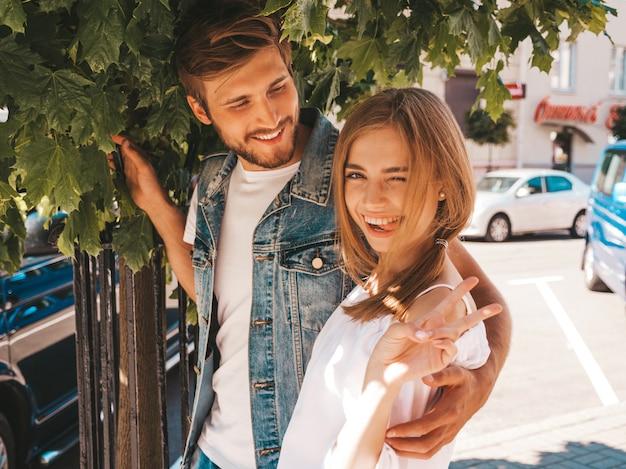 Glimlachend mooi meisje en haar knappe vriendje poseren in de straat in de buurt van boom.