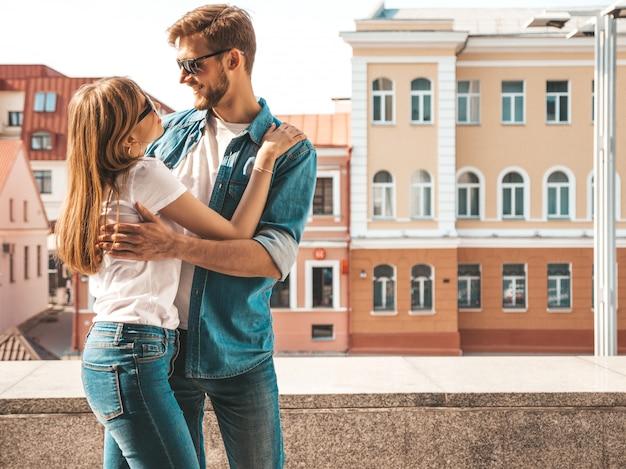Glimlachend mooi meisje en haar knappe vriendje. vrouw in casual zomer jeans kleding. . kijkend naar elkaar