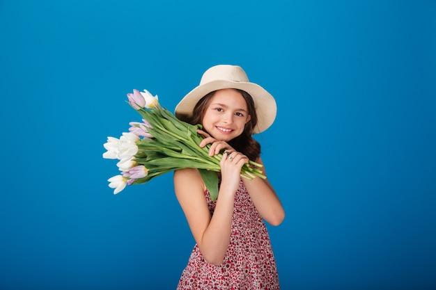 Glimlachend mooi meisje in hoed met boeket bloemen op haar schouder over blauwe achtergrond