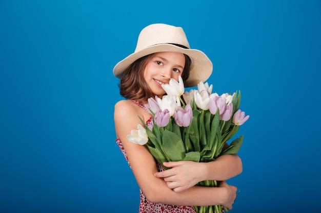 Glimlachend mooi meisje in hoed staande en boeket tulpen te houden over blauwe achtergrond