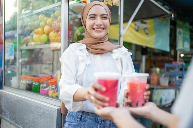 Glimlachend mooi meisje in sluier geeft twee kopjes fruitijs aan de klant