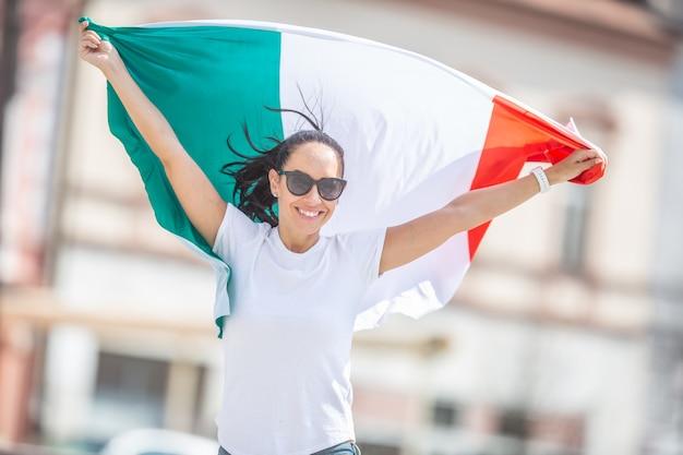 Glimlachend mooi meisje in zonnebril en wit t-shirt houdt italiaanse vlag op een straat vieren.
