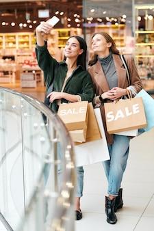 Glimlachend mooi meisje met papieren zakken met verkoop tekst selfie met vriend in winkelcentrum