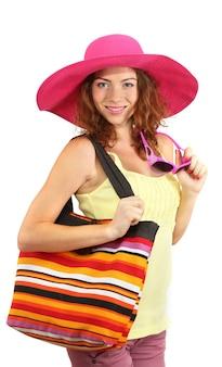 Glimlachend mooi meisje met strandhoed en zak op wit