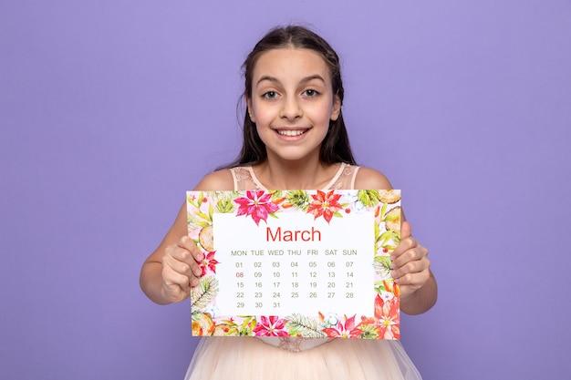 Glimlachend mooi meisje op de dag van de gelukkige vrouw met kalender geïsoleerd op blauwe muur