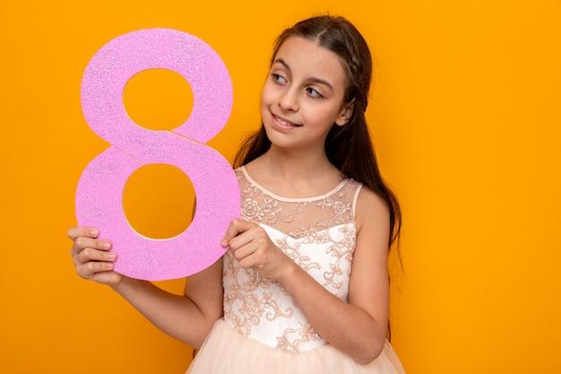 Glimlachend mooi meisje op een gelukkige vrouwendag die nummer acht vasthoudt en kijkt