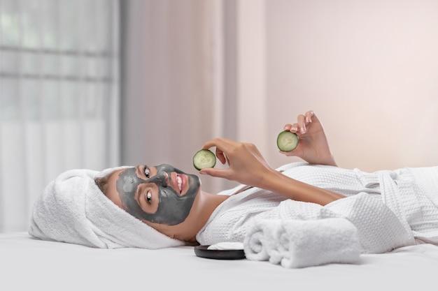 Glimlachend mooi model poseren met een kleimasker op haar gezicht terwijl ze op een bed ligt met twee plakjes