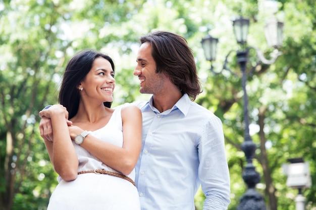 Glimlachend mooi paar dat buitenshuis flirt